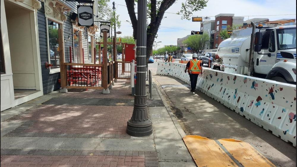 A worker walks alongside a barrier widening a sidewalk along Whyte Avenue