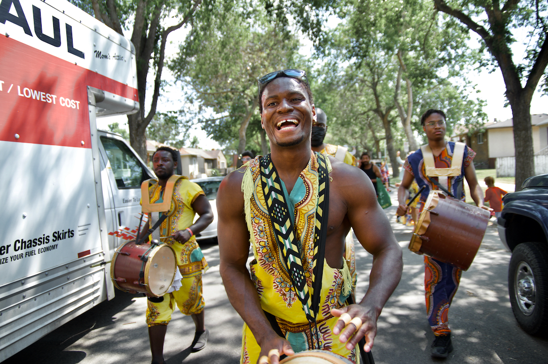 Drummers in African prints parade down a residential street
