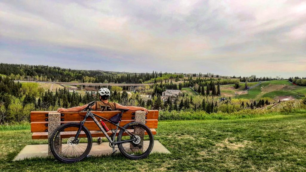 A man sits on a bench with a bike behind him, overlooking Edmonton.