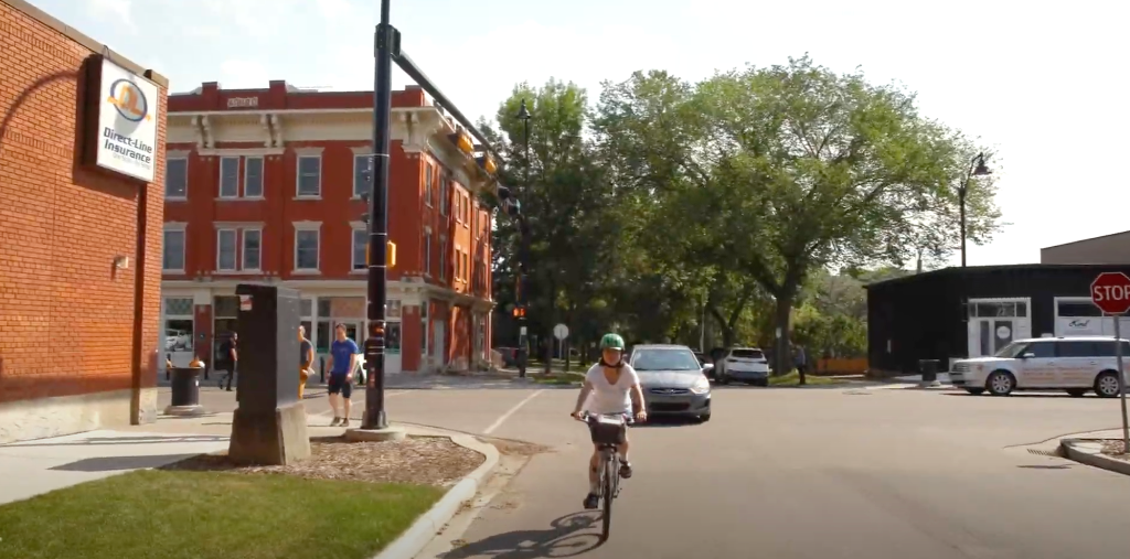 A cyclist is followed by a car in a screenshot from a video on safe streets for everyone