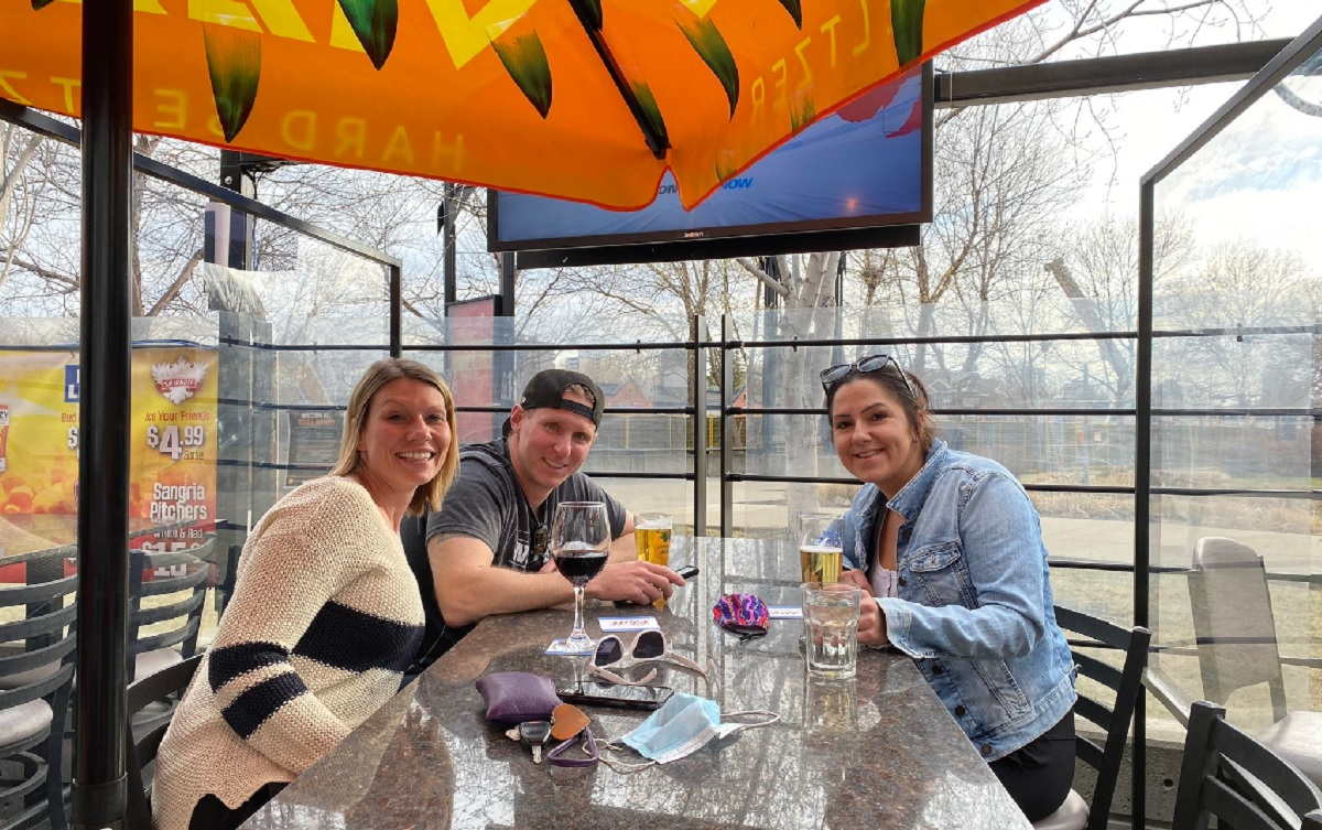 Three people sit at the now closed 1stRND patio