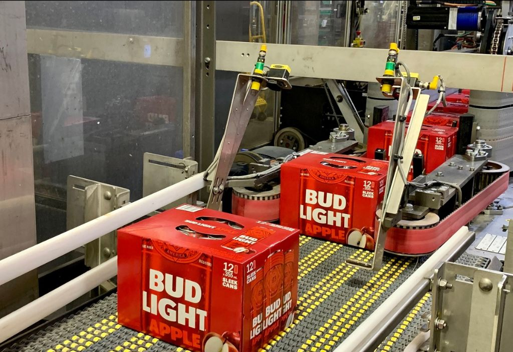 A photo of Bud Light Apple cans in boxes at a production facility.