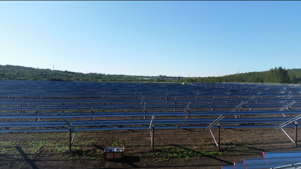 An array of racks for solar panels surrounded by trees