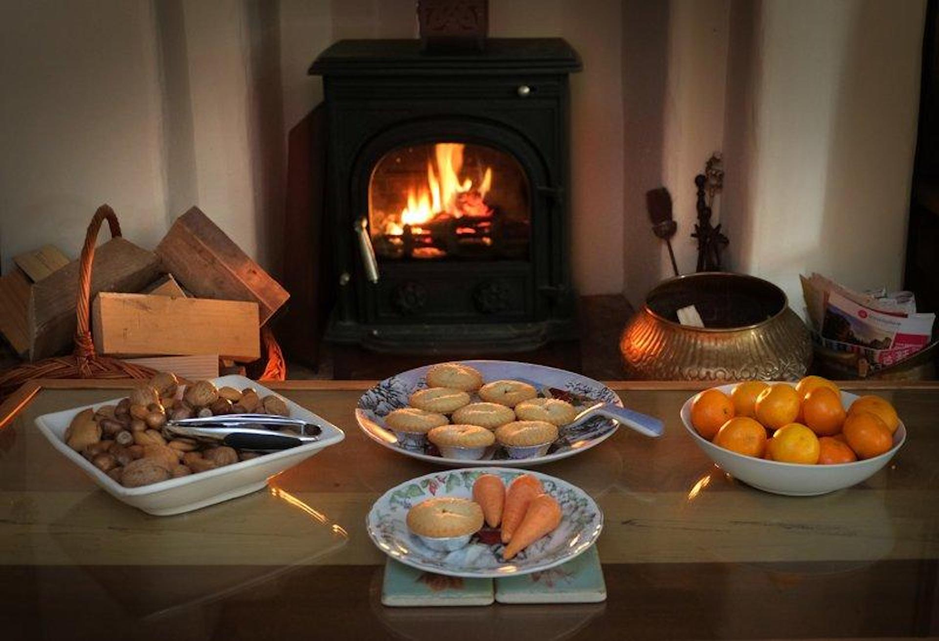 A feast for Father Christmas. in front of a burning coal fire a table is lined with plates filled with mince pies, fruit, nuts and a carrot for the reindeer.