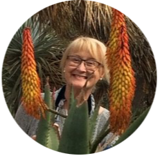 Dr. Tammie Bassford - A smiling white woman with short, blonde hair wearing eyeglasses. In the foreground is a cactus plant.