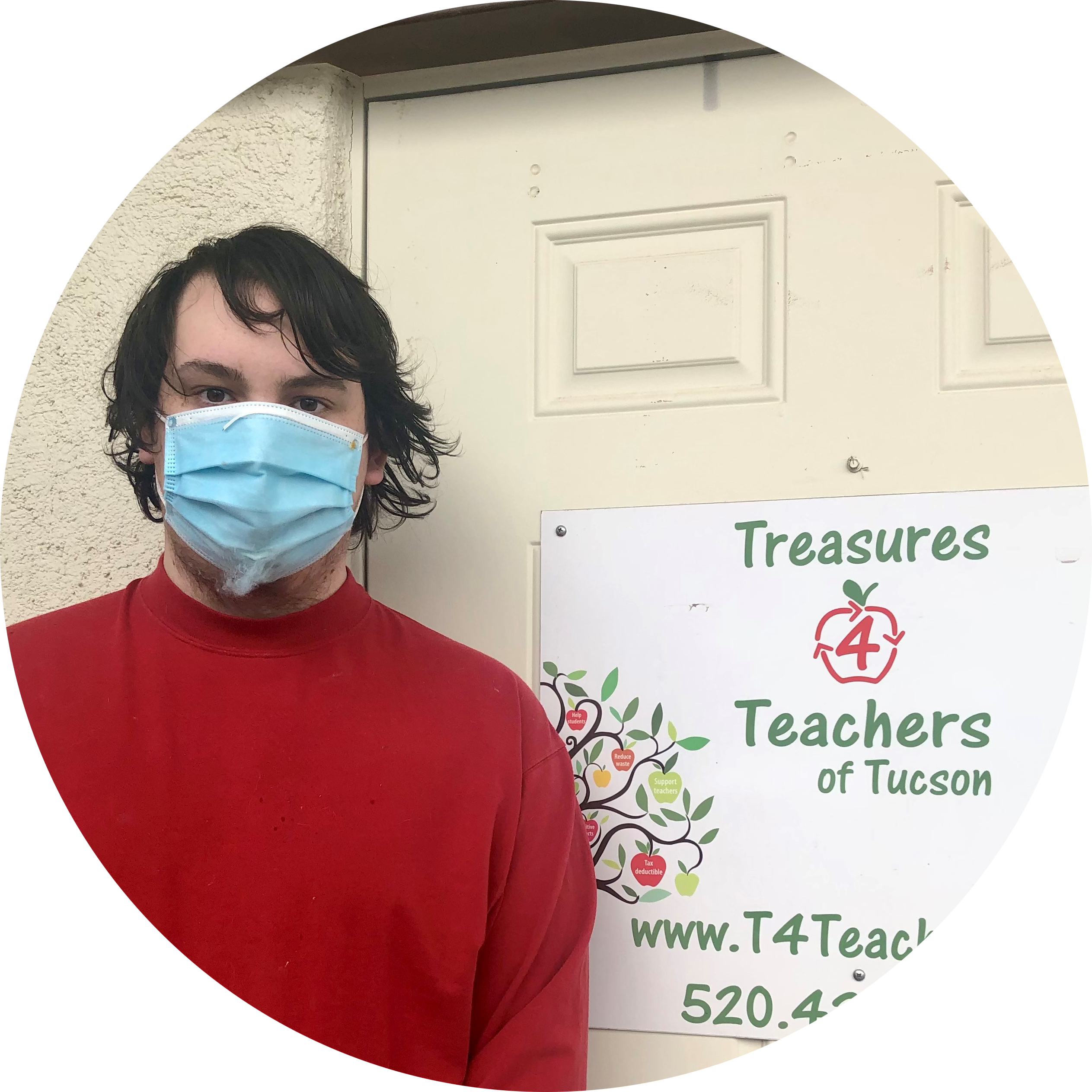 Photo of Dylan Gallaway - a young white man wearing a red shirt and a medical mask standing in front of the door to Treasures 4 Teachers of Tucson