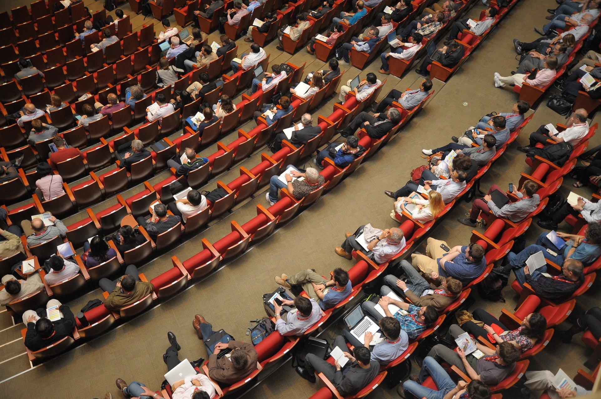 Vista aèria d'una sala de conferències amb assistents a les butaques.