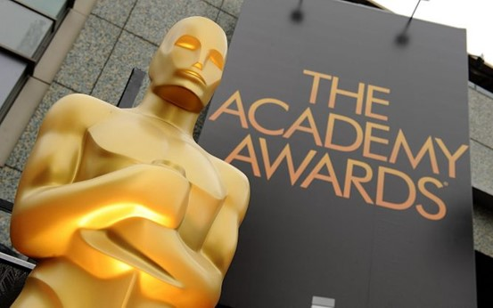 """An Oscar in from of a sign that reads """"The Academy Awards"""""""