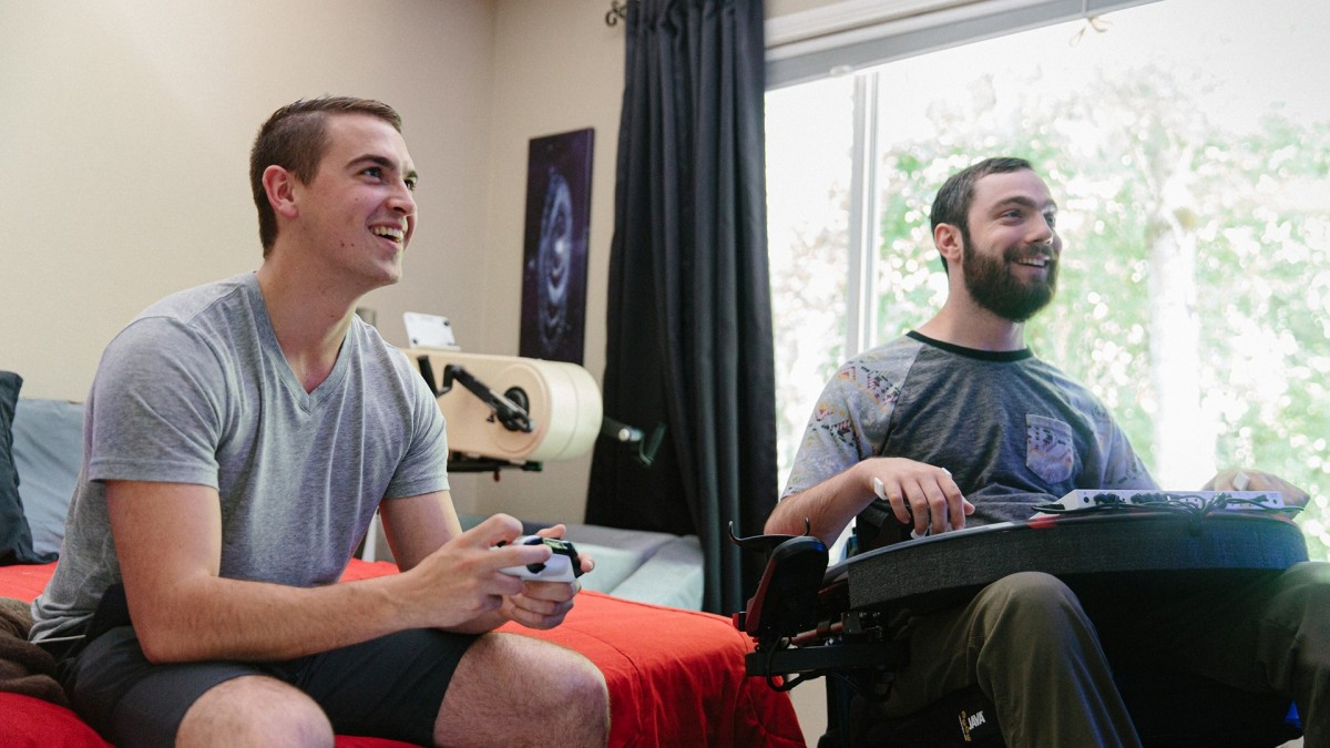Two gamers using an Xbox, one with accessibility controls