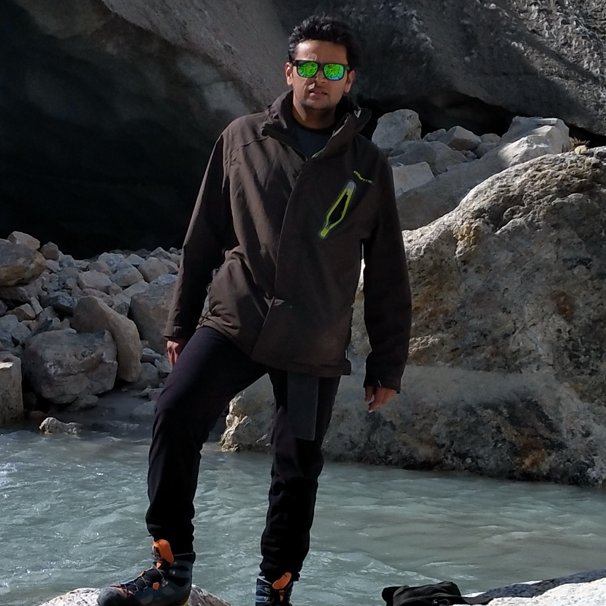 Saurabh in hiking clothes standing in front of rocks and a river