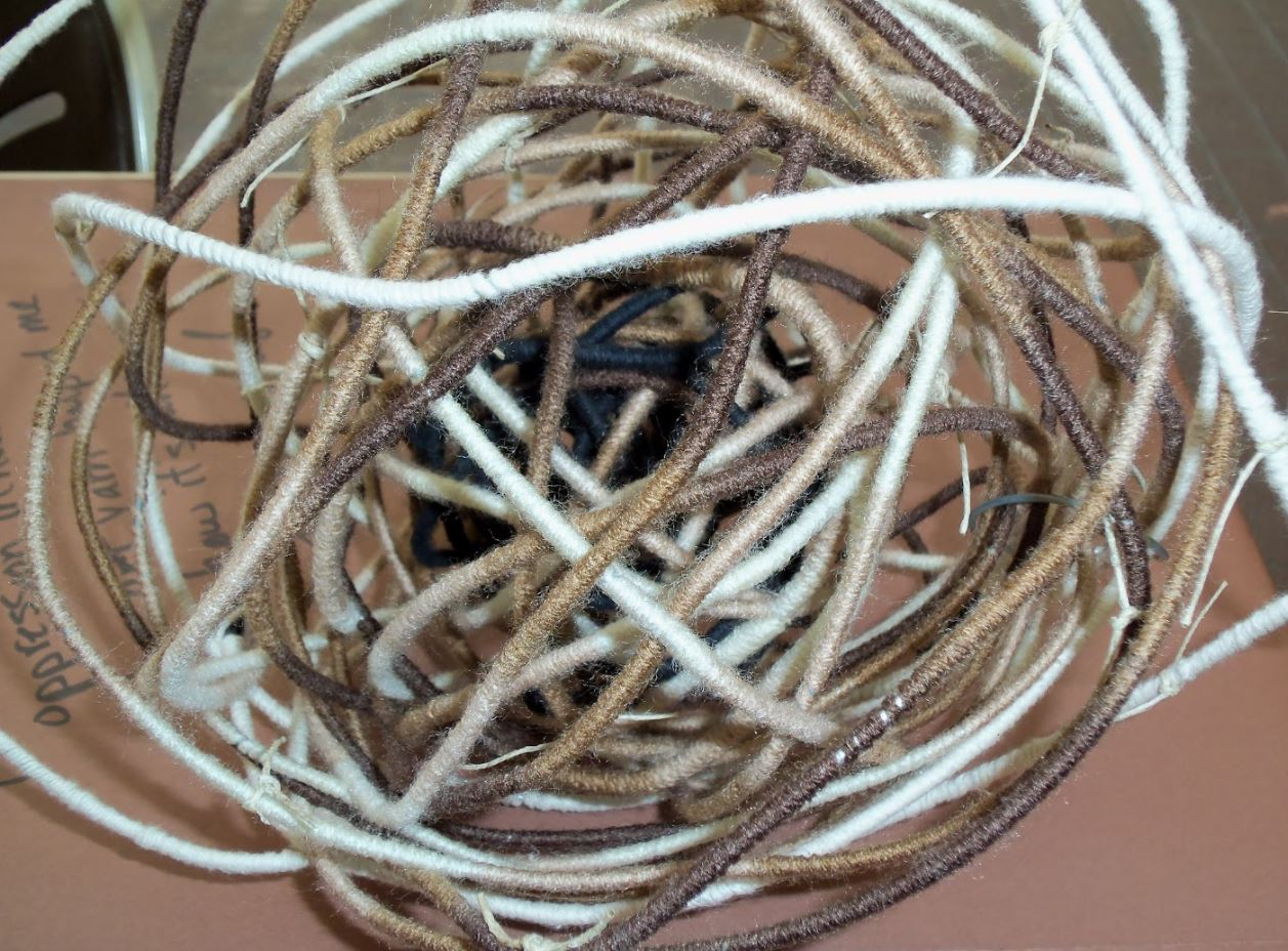 loose ball of twine with black in the center and beige on outer portion