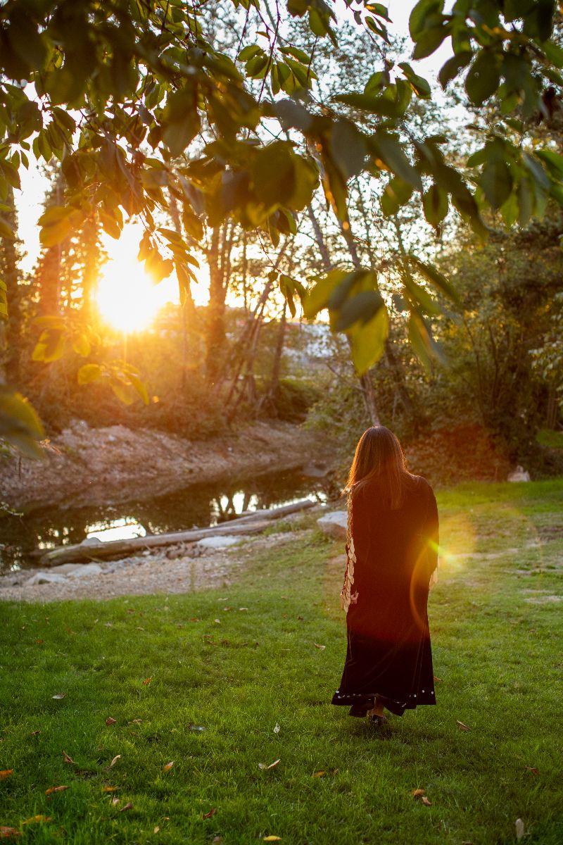 Auntie Shellene, Skwét7siya, walks away fro camera among foliage