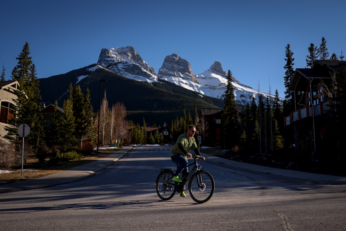 A cyclist rides through the town of Canmore, Alta., with the Three Sisters mountains in the background