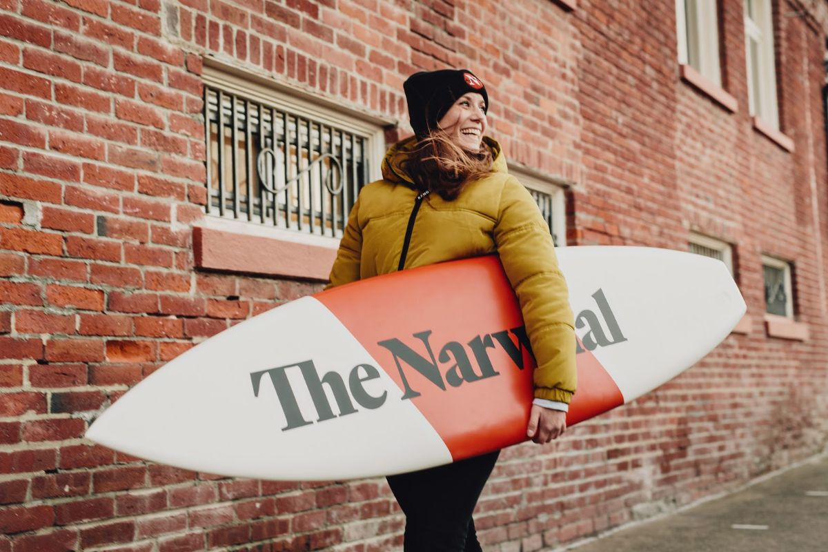Managing editor Carol Linnitt holding a Narwhal-branded surfboard