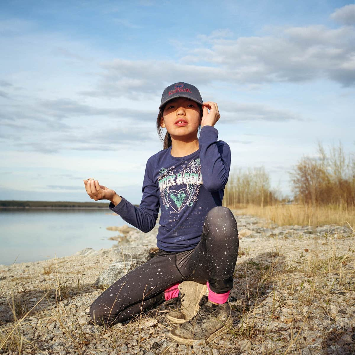 Aalaiyah wears a Keeyask dam hat while she plays on riprap-enforced river banks that surround the community of Split Lake