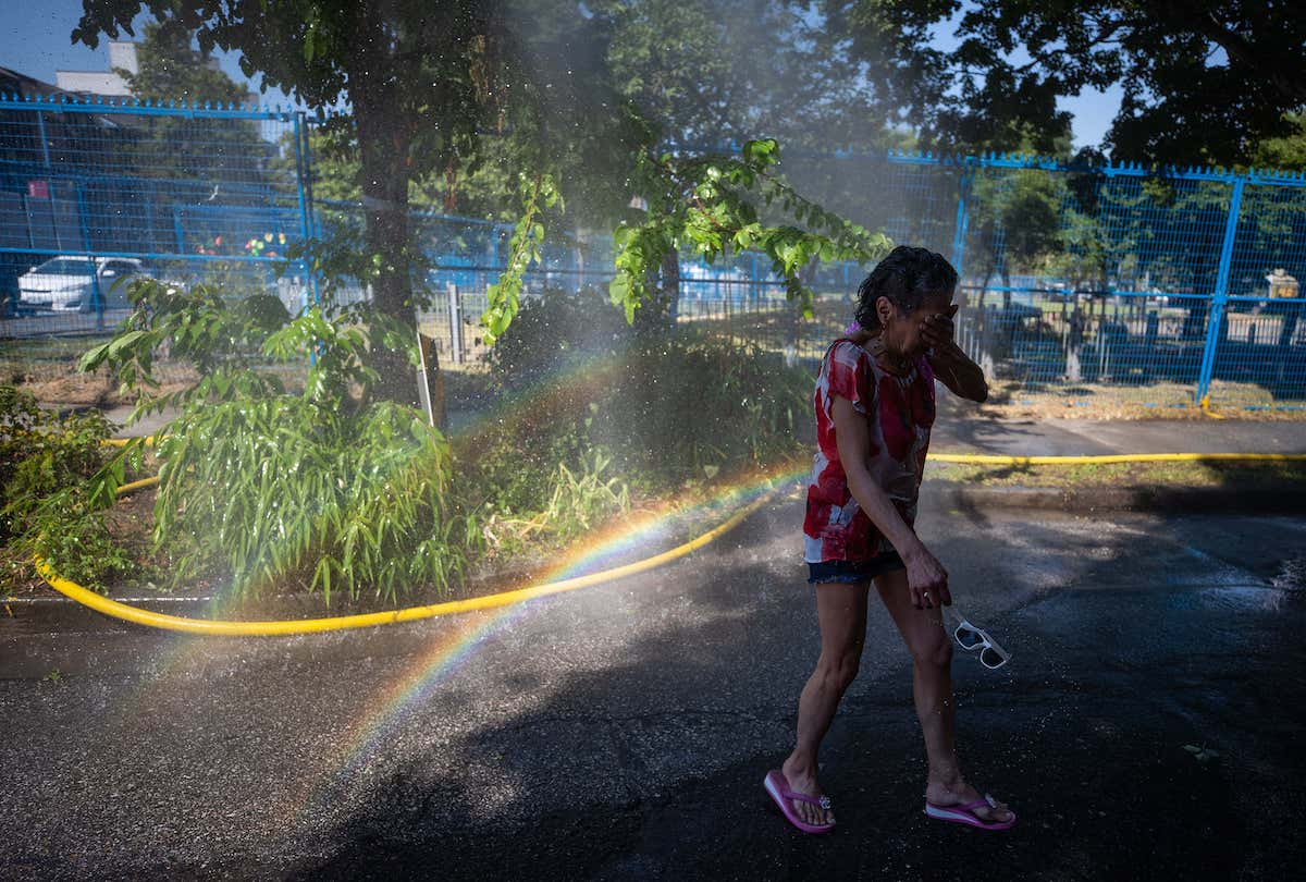 A woman cools off at a temporary misting station in the Downtown Eastside of Vancouver