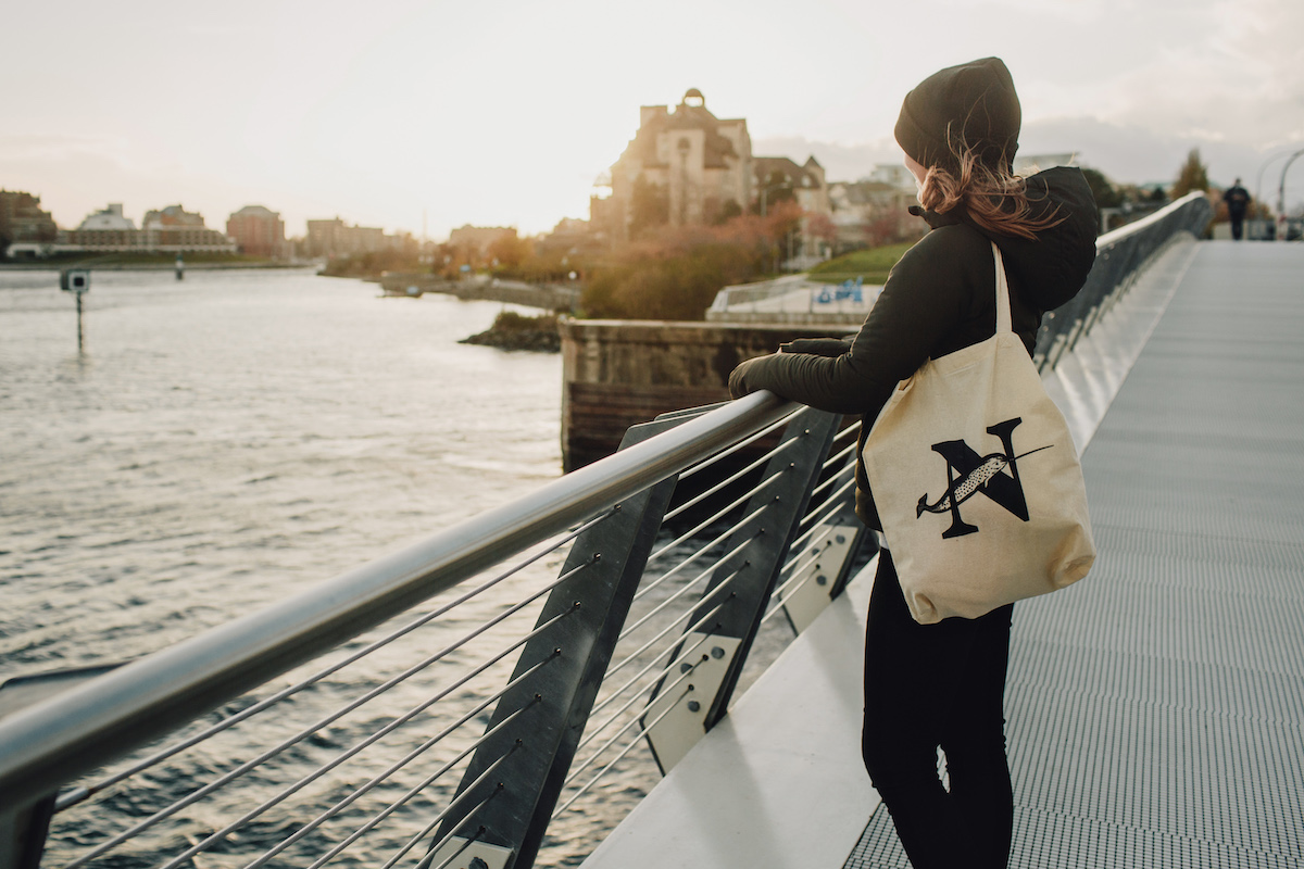 Editor-in-chief Emma Gilchrist looks out on a bridge while rocking a Narwhal tote bag