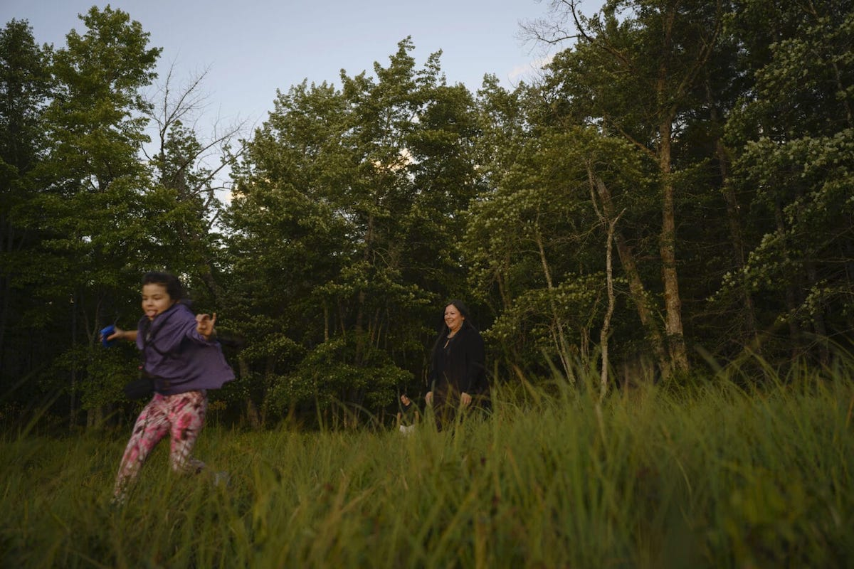 A mother laughs while watching her kid run through the grass on the edge of a forest in Nova Scotia. Photo: Darren Calabrese / The Narwhal