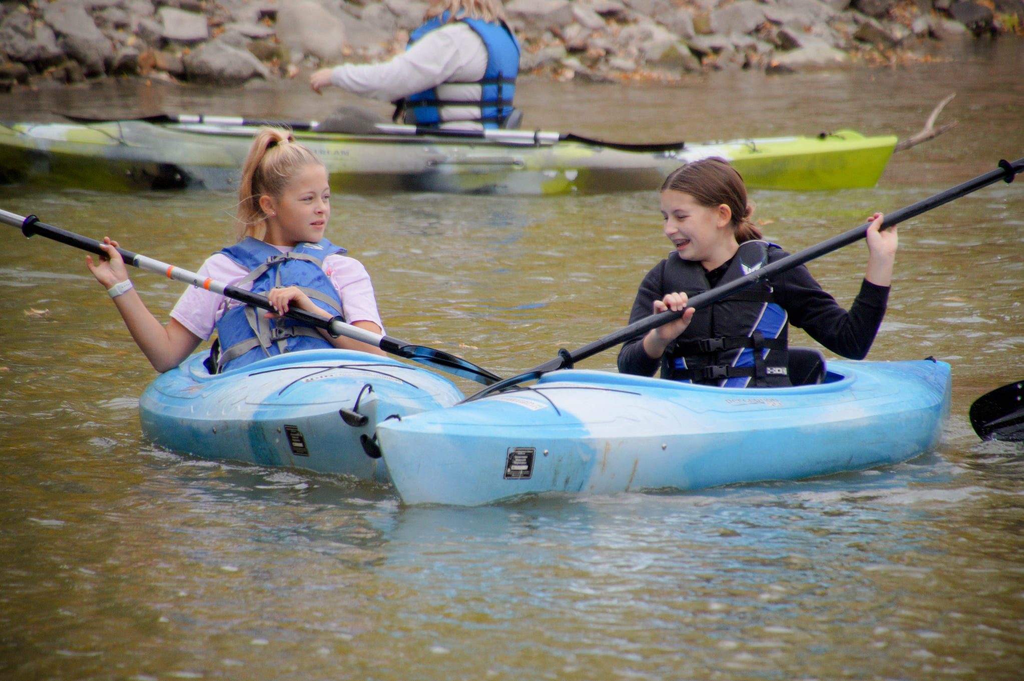 Two students paddling aside one another on the Red River in Moorhead, MN.