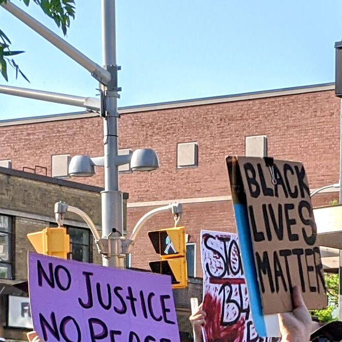 """Students hold up handmade signs saying """"No justice; no peace"""" and """"Black lives matter"""" during a peaceful protest"""