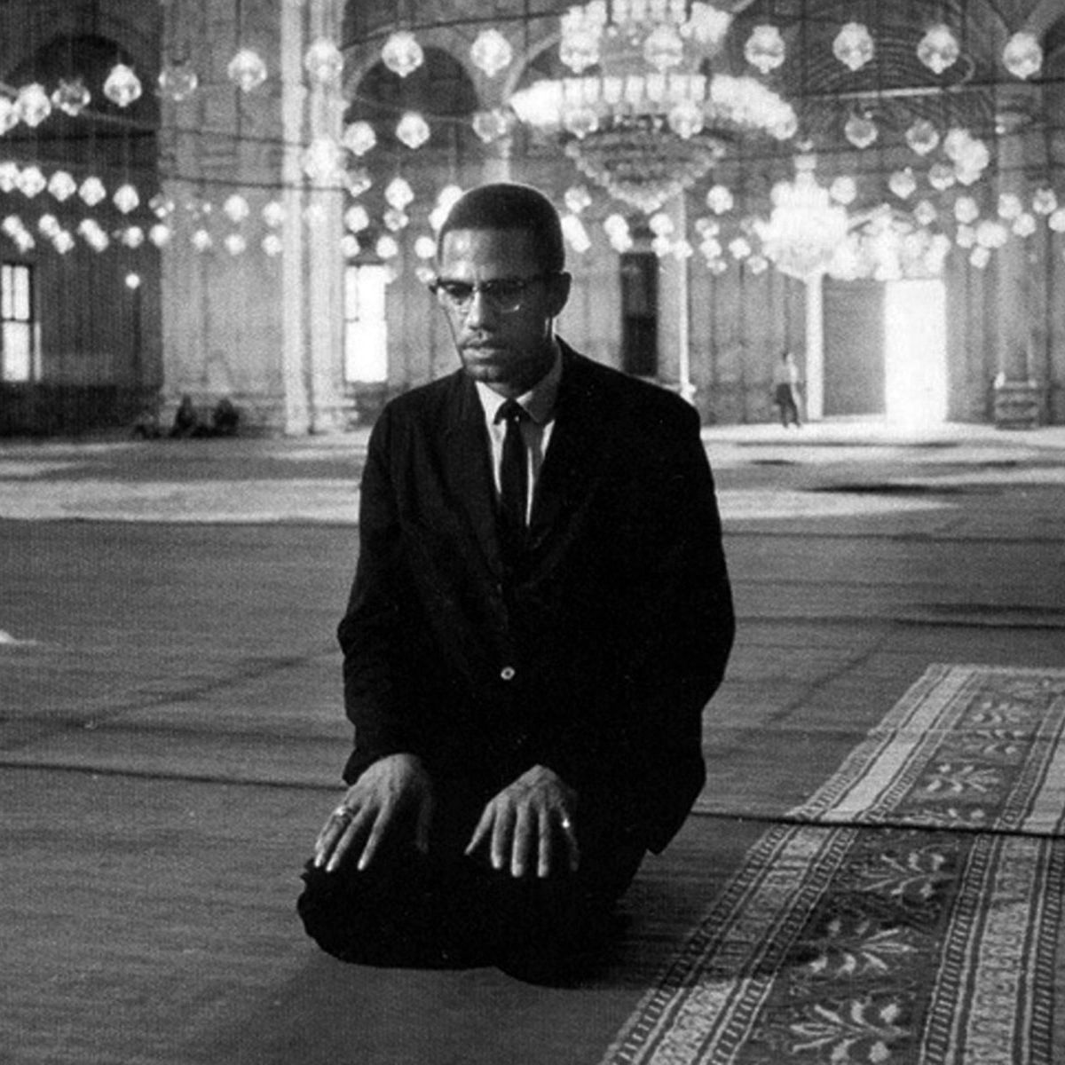 Malcolm X kneels in a black suit during his 1964 pilgrimage to Mecca