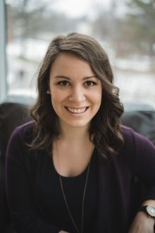 Katie Gingerich smiles for a photo while seated. She is wearing a navy blue sweater, long silver necklace, and her shoulder-length brown hair is curled slightly.