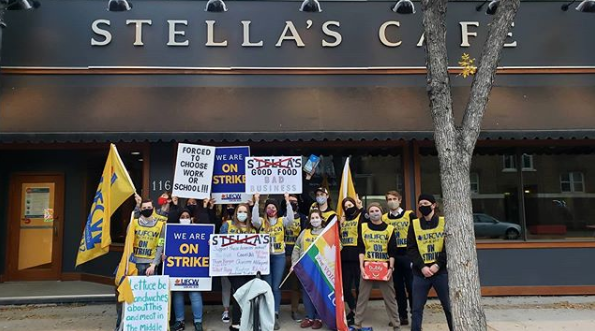 "Image of group of picketers in front to Stella's restaurant on Sherbook.  The group of about 15 people holding signs that read ""We are On Strike"" and ""Forced to Choose Work or School"", also holding flags, wearing UFCW vests and some other hand written signs"