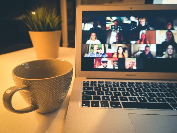 Coffee mug next to a computer showing an online meeting