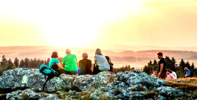 group of people sitting on large boulders facing a sunrise