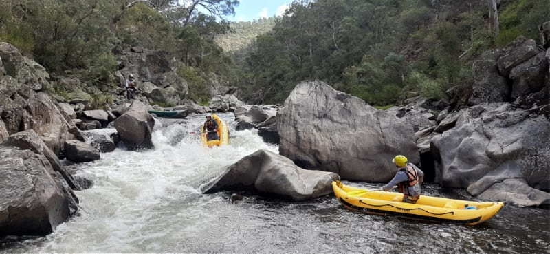 2 paddlers in yellow water craft on a river