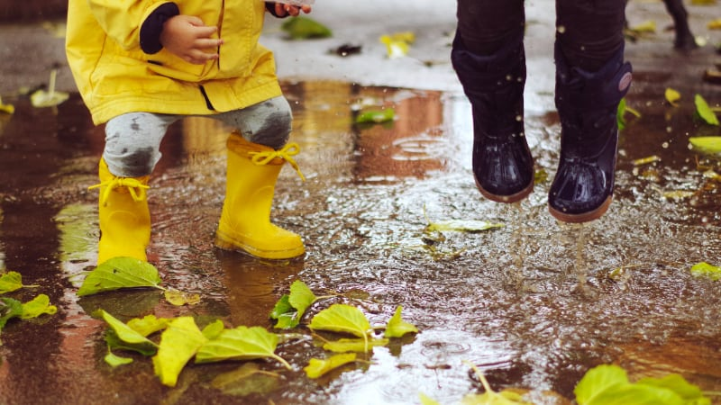 small person in yellow raincoat & yellow gumboots and black gumboots jumping in puddle