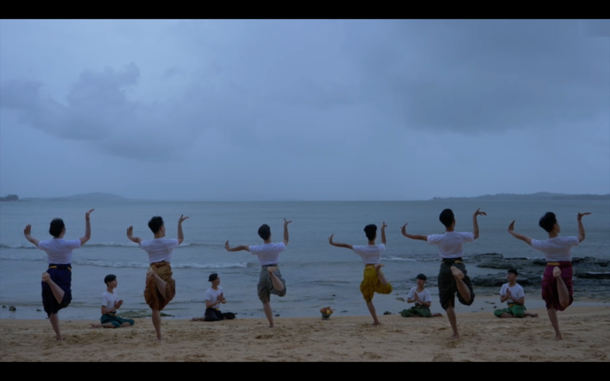 """A screenshot from NATYARASA's project-in-progress """"A Deepest Blue,"""" showing ten dancers in white shirts and Cambodian-style pants at a beach in Cambodia. The sky is filled with large clouds and is a similar color to the bluish-gray ocean. We see the backs of six of the dancers, who balance on their left legs and lift their bent arms and wrists to the sky while four of the dancers who are kneeling on the sand face them."""