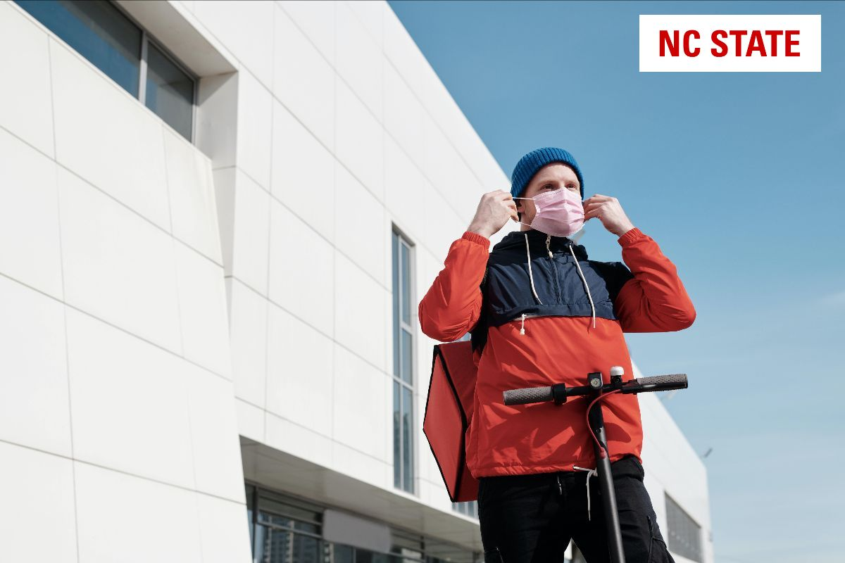 Man in red and blue putting on a face mask in front of a building