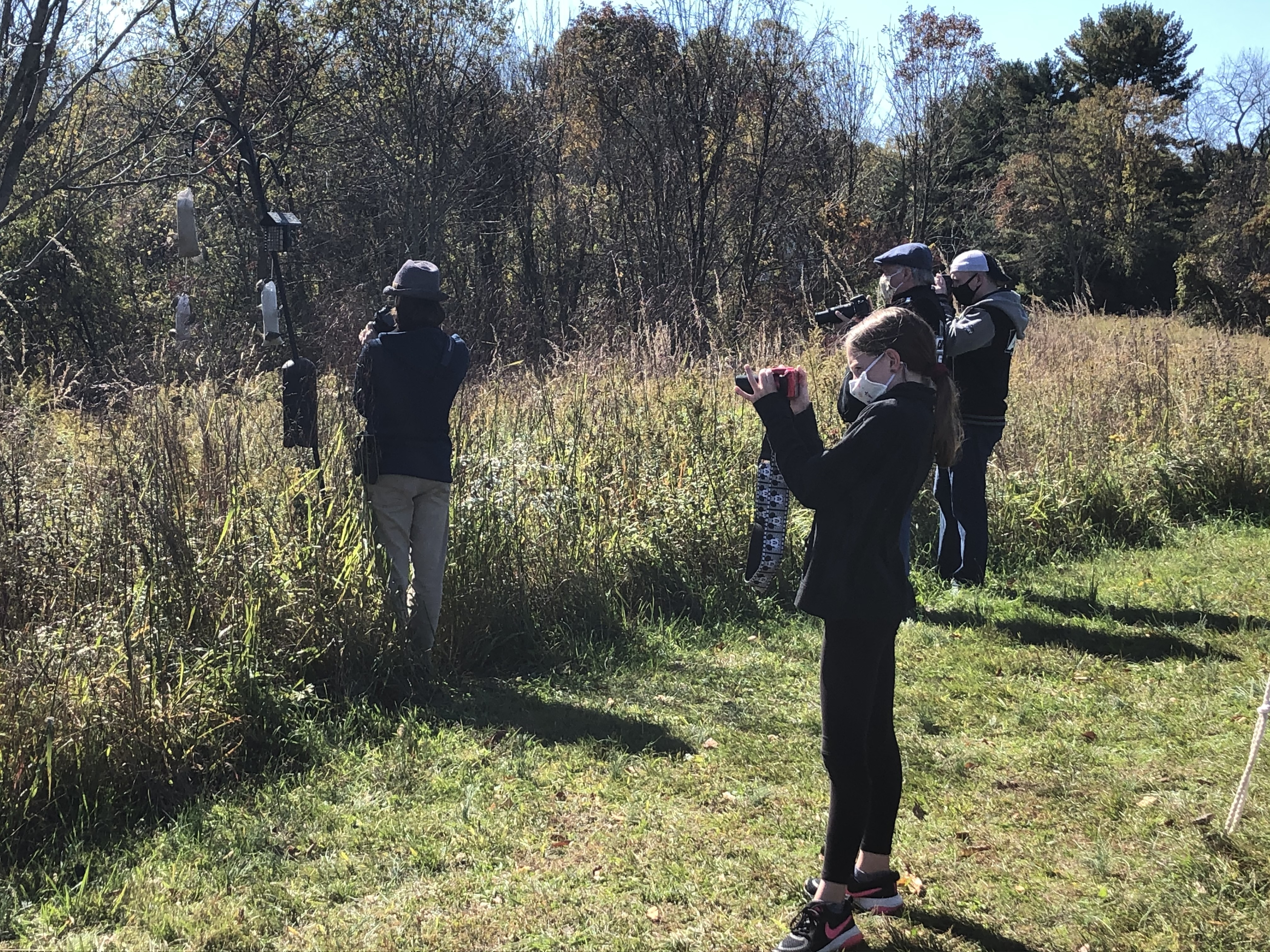 DOS Youth Birders watching some pine siskins. Participants are distanced and wearing masks.