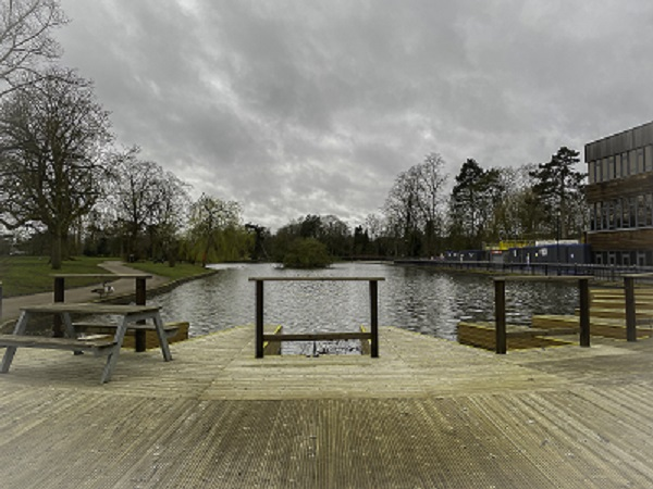 Grey sky reflected in the lake from wooden decking