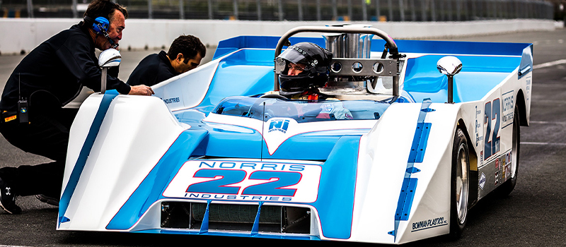 Blue race car with driver wearing a helmet talking to his team on the track