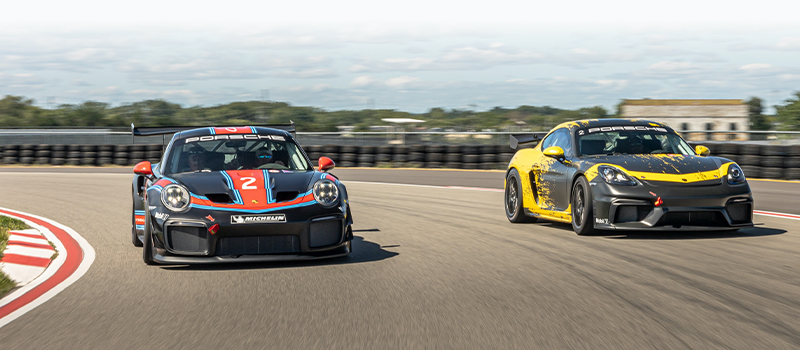 Two racecars going around a curve in a racetrack