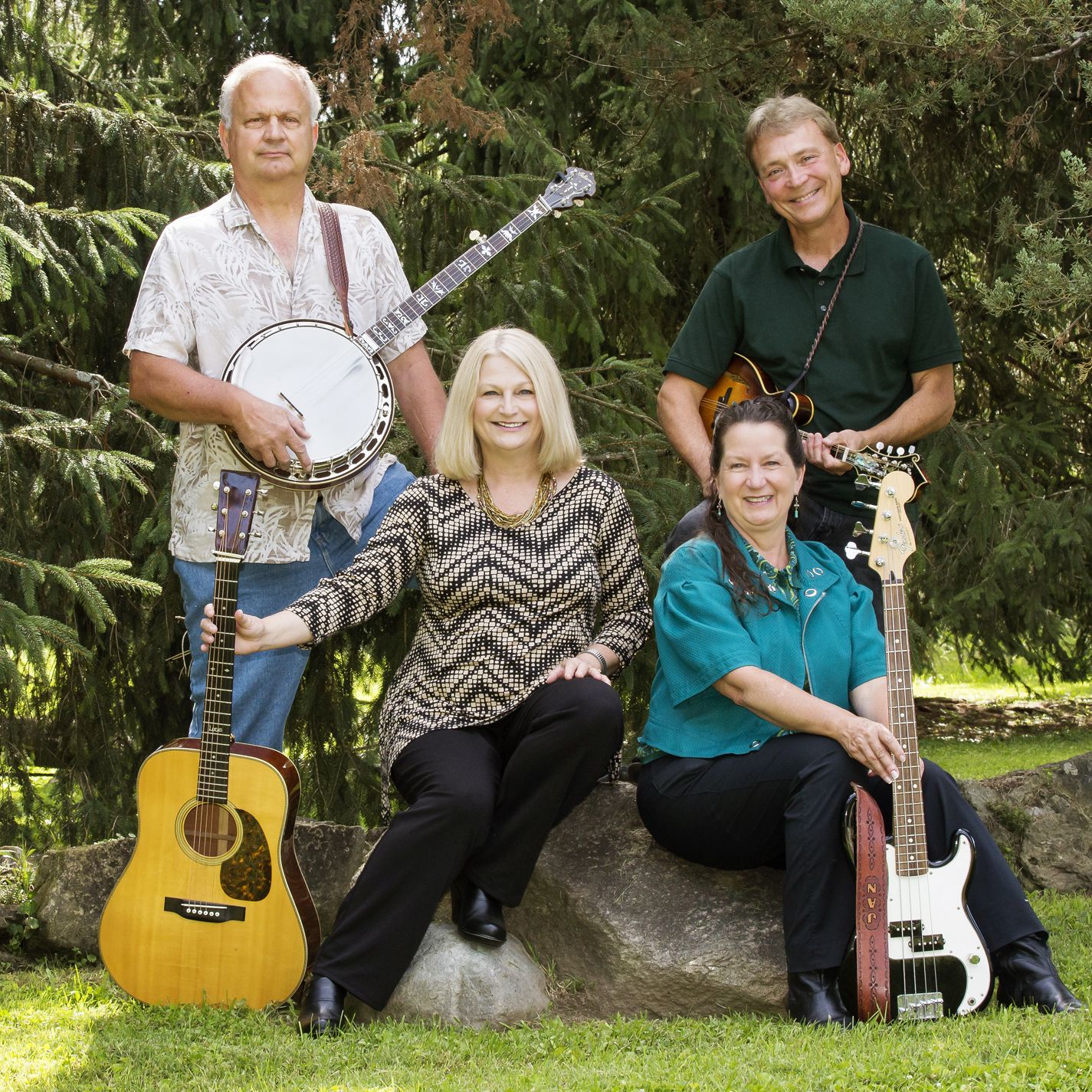 Photo of the Banister Family Bluegrass Band in a park/outdoor setting with grass and evergreen trees surrounding them: Two men standing, one holds a banjo (left), the other holds a mandolin (right). Two women are seated on a boulder, each with a guitar.