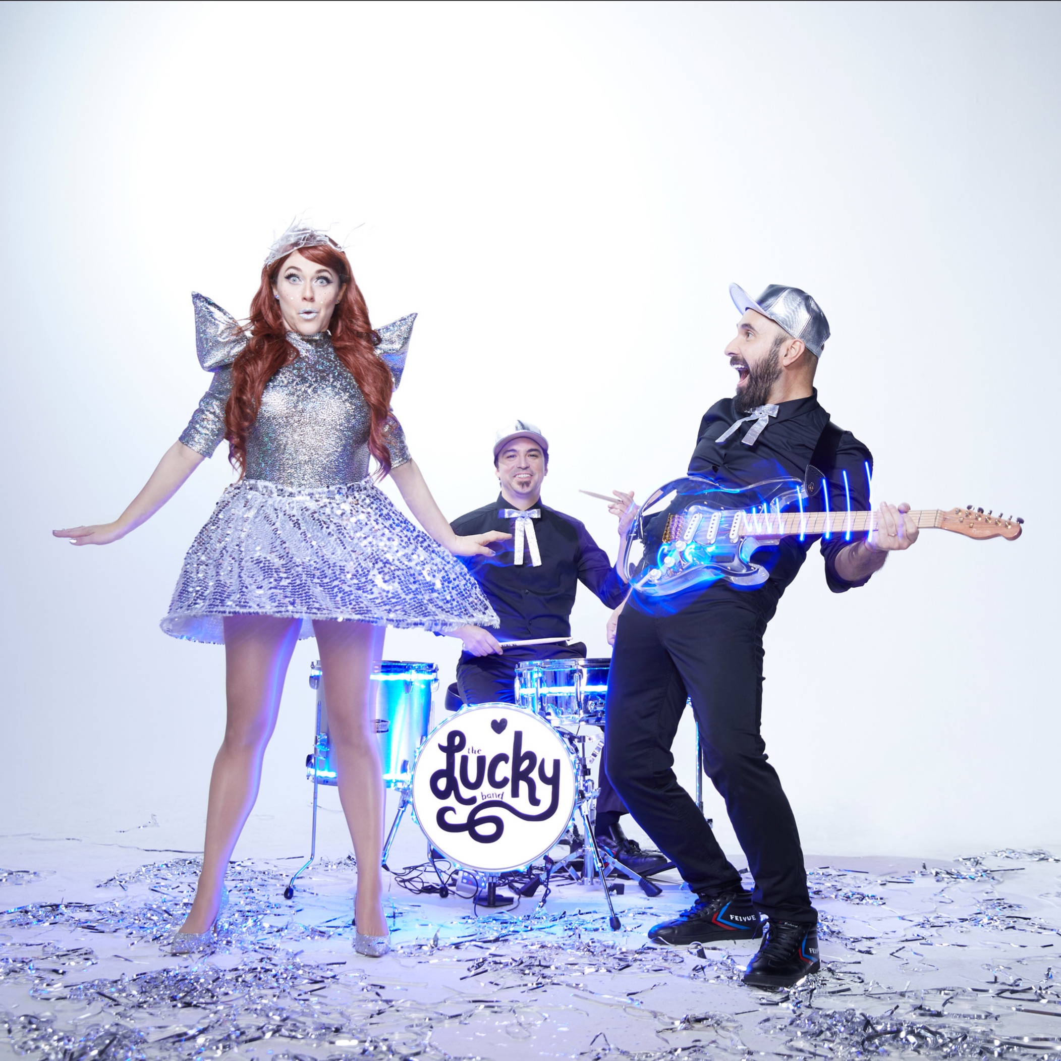 Image of The Lucky Band: A woman with red hair and a sparkling silver dress stands facing the audience with a surprised look; a man with a silver cap and black outfit leans back, holding a guitar and turns to look in amusement at her; a drummer wearing black smiles from the background