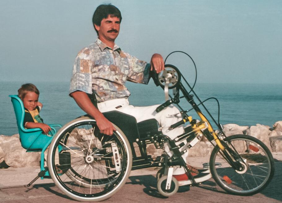 Reiner mit seinem Sohn und Handbike am Meer