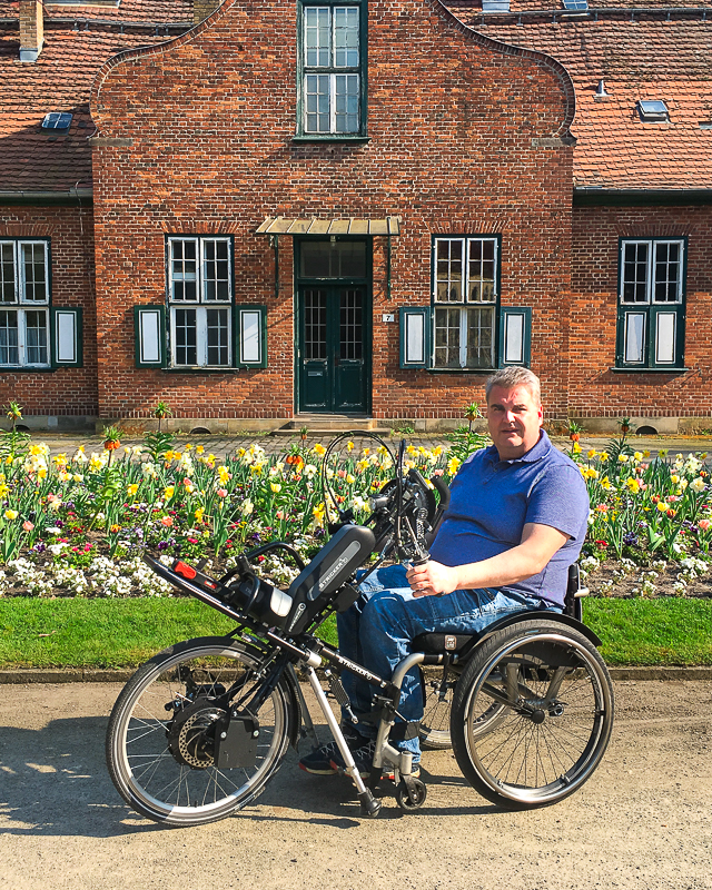 Our sales representative Jan in front of a beautiful garden with his handbike and waldkilo carrier rack.