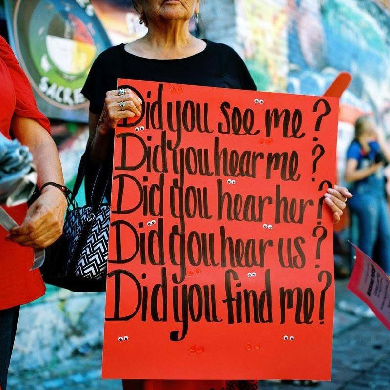 Image shows a the bottom half of a woman, holding a sign that reads