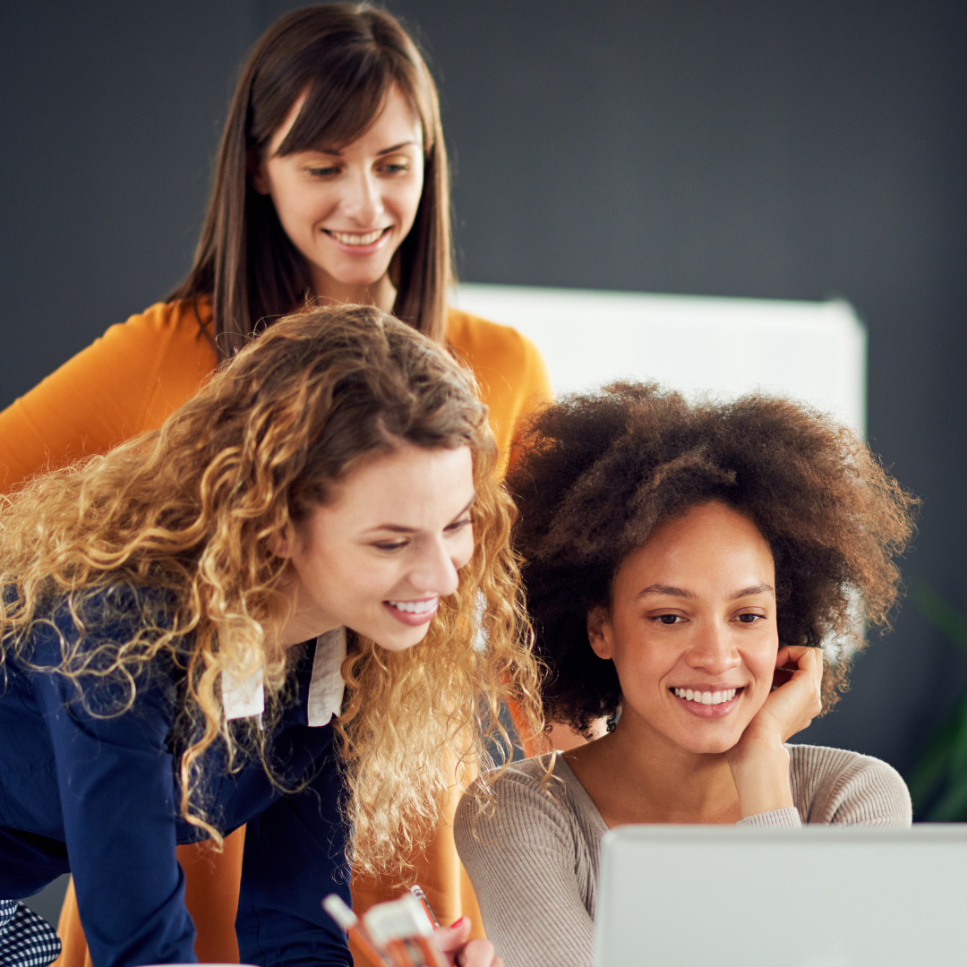 Three young women look at a laptop screen and smile.