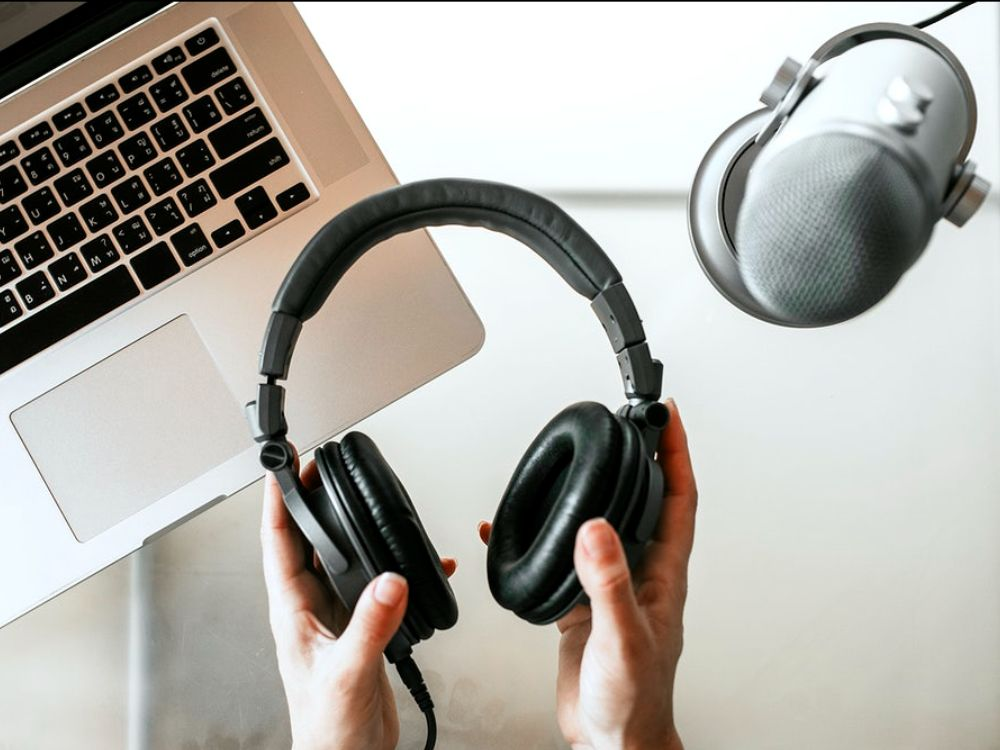Hands holding headphones, to the right hand side is a studio microphone and in the background is a laptop