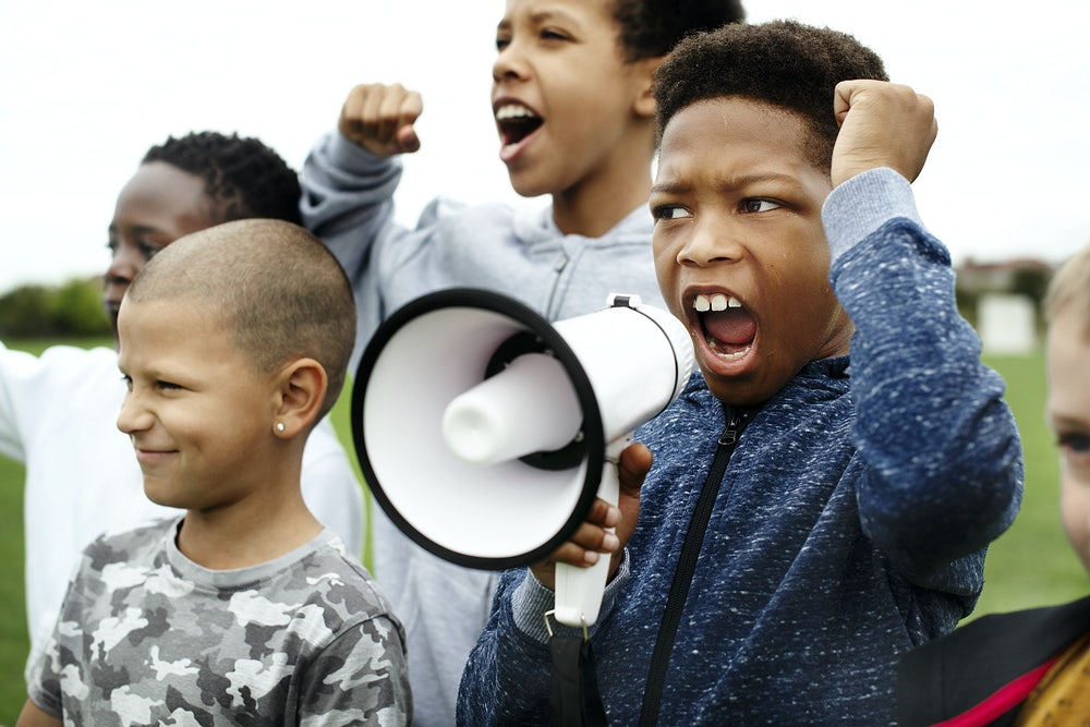 Children outside, one child is holding a megaphone and speaking through it