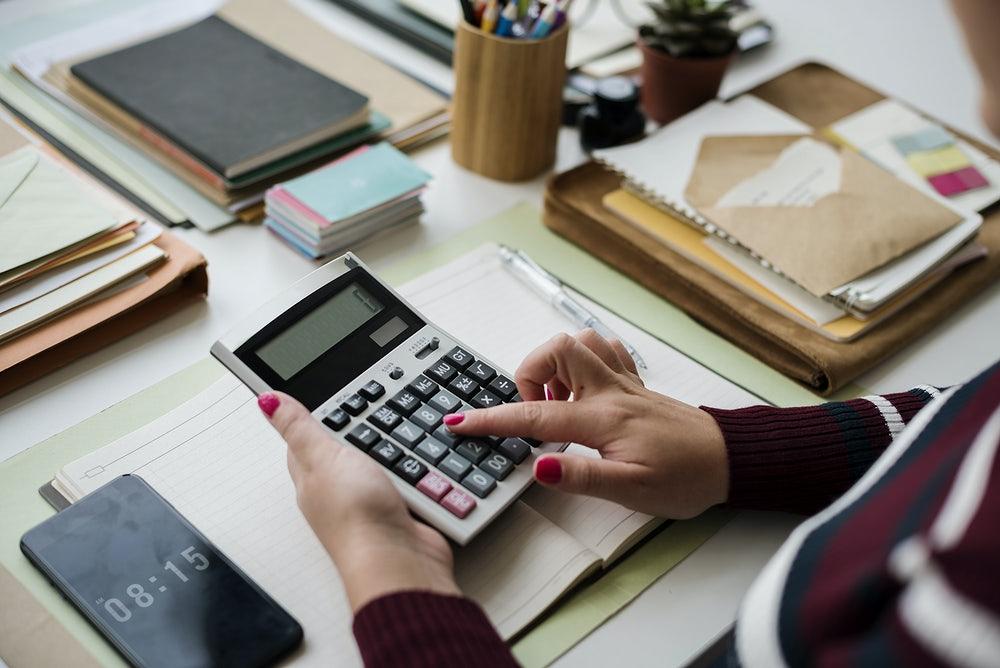 A hand using a calculator