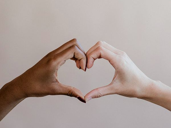 Two hands from separate people, together forming a love heart