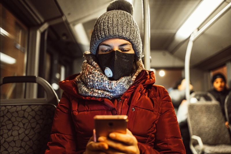 Masked woman looking at phone on bus