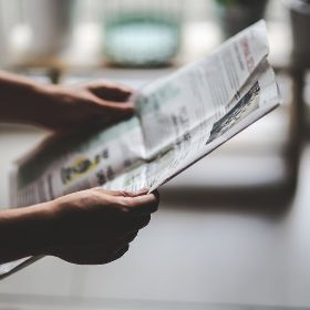 Hands holding a newspaper open