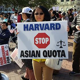 Woman holding 'Havard, Stop Asian Quota' sign